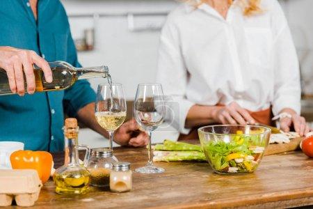 Photo pour Image recadrée de mari mature versant du vin dans des verres, femme coupant des légumes dans la cuisine - image libre de droit