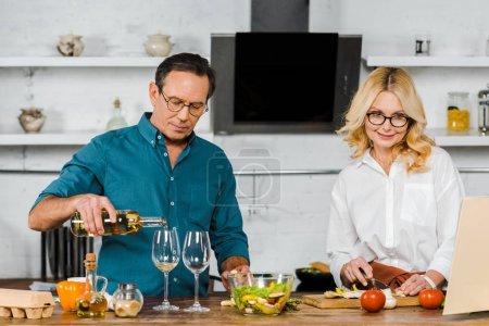 Photo pour Beau mari mature, verser le vin dans des verres, légumes coupe séduisante femme dans la cuisine - image libre de droit