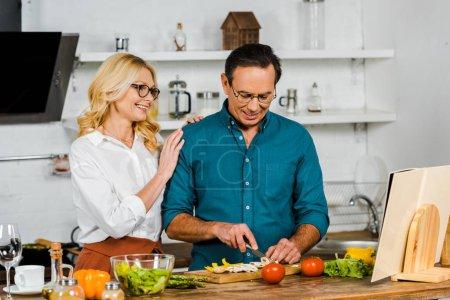 Photo pour Mature femme étreignant mari pendant qu'il coupe les légumes en cuisine - image libre de droit