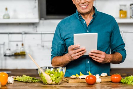 Photo for Cropped image of smiling mature man using tablet while cooking in kitchen - Royalty Free Image