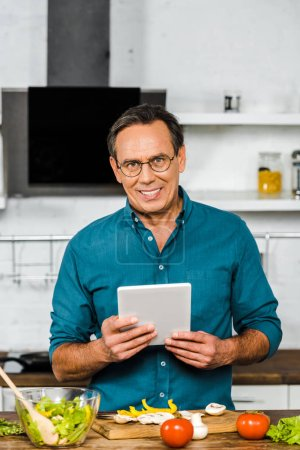 Photo for Smiling handsome mature man using tablet while cooking in kitchen, looking at camera - Royalty Free Image