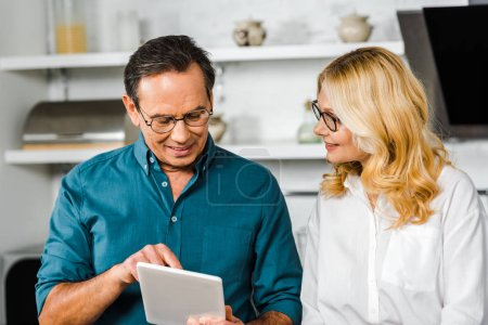 mature husband showing something on tablet to wife in kitchen