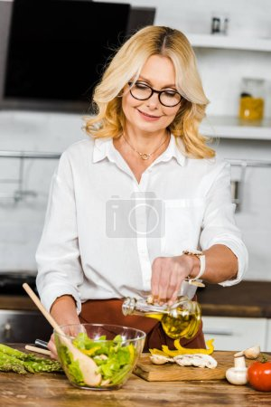Photo for Attractive mature woman pouring oil into bowl with salad in kitchen - Royalty Free Image
