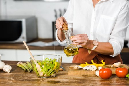 Photo for Cropped image of mature woman pouring oil into bowl with salad in kitchen - Royalty Free Image