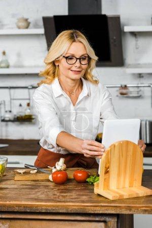 Foto de Hermosa mujer madura leyendo receta de tableta durante la cocción en la cocina - Imagen libre de derechos