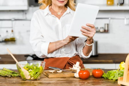Photo for Cropped image of mature woman reading recipe from tablet during cooking in kitchen - Royalty Free Image