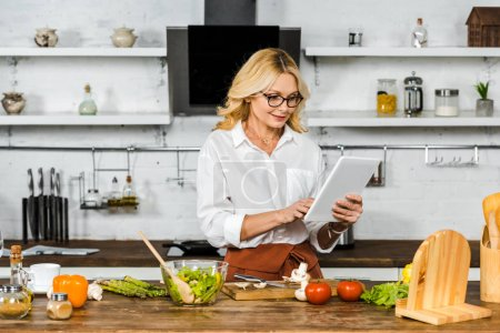 Photo for Attractive mature woman in glasses reading recipe from tablet during cooking in kitchen - Royalty Free Image