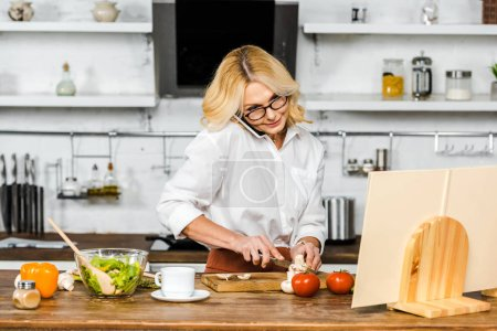 Photo for Attractive mature woman talking by smartphone, cutting vegetables and looking at recipe book in kitchen - Royalty Free Image