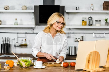 Photo for Attractive mature woman looking at recipe book while cutting mushrooms in kitchen - Royalty Free Image