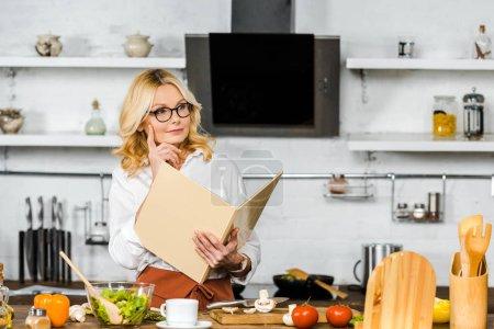 Photo pour Songeuse belle femme mature, lecture de livre de recettes pour la cuisson dans la cuisine - image libre de droit