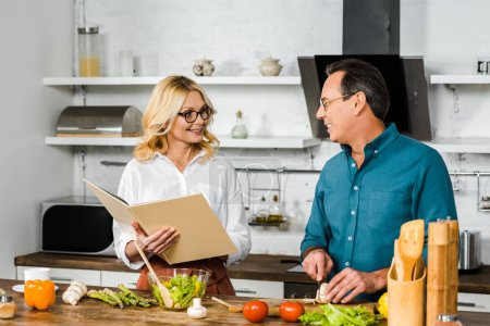 Photo for Mature wife and husband cooking together with recipe book in kitchen, looking at each other - Royalty Free Image