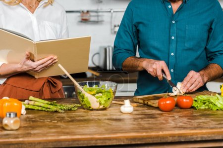 Photo for Cropped image of mature wife and husband cooking together with recipe book in kitchen - Royalty Free Image