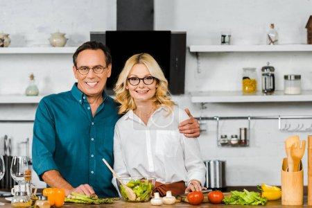 Photo pour Sourire de femme mature et mari étreindre et regardant la caméra dans la cuisine - image libre de droit