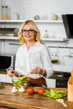 Photo for Smiling beautiful middle aged woman mixing salad in glass bowl in kitchen and looking at camera - Royalty Free Image