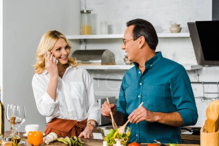 mature wife talking by smartphone and husband mixing salad in bowl in kitchen