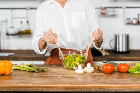 Photo for Cropped image of mature woman mixing salad in glass bowl in kitchen - Royalty Free Image