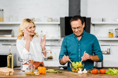 attractive mature wife talking by smartphone and handsome husband mixing salad in bowl in kitchen