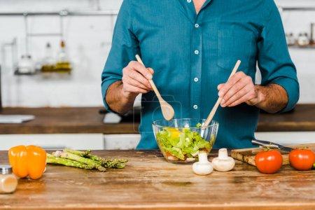 Photo pour Image recadrée de l'homme mûr mélangeant la salade dans un bol dans la cuisine - image libre de droit