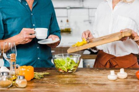 Photo pour Cropped image de légumes mettre femme mature dans le bol et mari tenant la tasse de thé dans la cuisine - image libre de droit