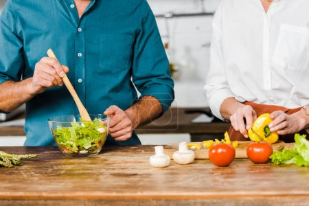 Photo for Cropped image of mature wife and husband cooking salad together in kitchen - Royalty Free Image