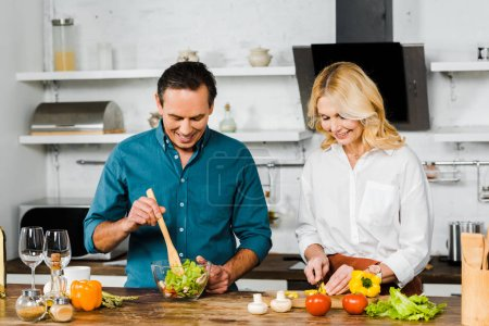 Photo for Mature wife and husband cooking organic salad together in kitchen - Royalty Free Image