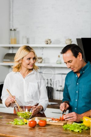 Photo for Mature wife and husband cooking healthy salad together in kitchen - Royalty Free Image
