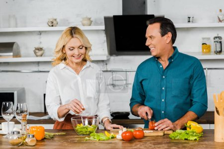 Photo for Smiling mature wife and husband cooking salad in kitchen - Royalty Free Image