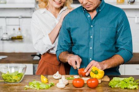 Photo pour Image recadrée de mari étreindre femme mature pendant qu'il cuisine salade dans cuisine - image libre de droit