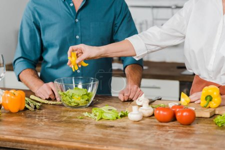 cropped image of mature wife and husband preparing salad together in kitchen