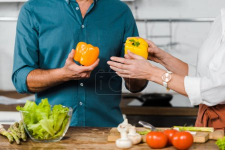 Photo for Cropped image of mature wife giving bell peppers to husband for cooking salad in kitchen - Royalty Free Image