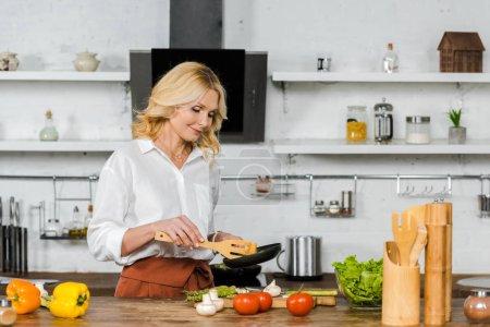 jolie femme âgée moyenne cuisson des légumes à la poêle dans la cuisine
