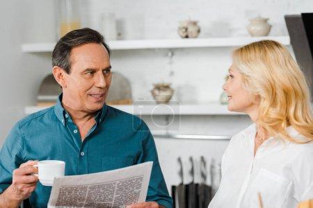 Photo pour Femme mûre regardant mari dans la cuisine, il tenant une tasse de thé et de journal - image libre de droit