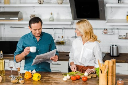 Photo for Attractive mature wife cutting vegetables and husband reading newspaper in kitchen - Royalty Free Image