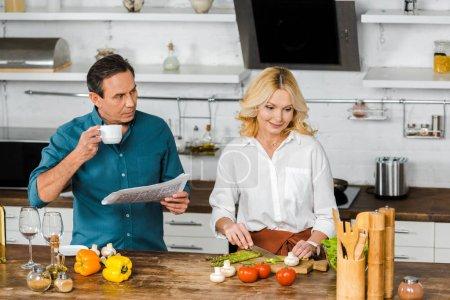 Photo pour Vue grand angle de la cuisine femme mature et mari lecture journal dans la cuisine - image libre de droit