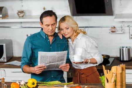 Photo pour Mature femme tenant la tasse de thé et de mari en lisant le journal dans la cuisine - image libre de droit