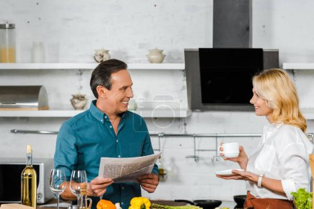 smiling mature wife holding cup of tea and husband reading newspaper while cooking in kitchen