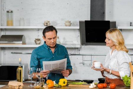 Photo pour Mature femme tenant la tasse de thé et de mari en lisant le journal pendant la cuisson dans la cuisine - image libre de droit