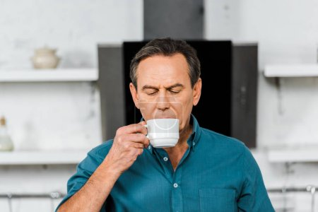 Photo for Handsome middle aged man drinking tea in kitchen - Royalty Free Image