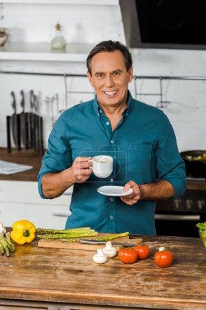 Photo pour Bel homme âgé moyen souriant tenant la tasse de café et de regarder la caméra dans la cuisine - image libre de droit