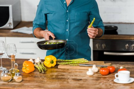 Photo for Cropped image of middle aged man cooking vegetables on frying pan in kitchen - Royalty Free Image