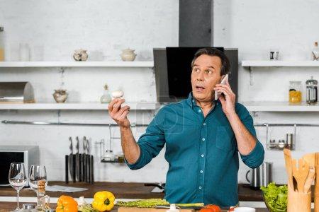 schöner Mann mittleren Alters, der in der Küche mit dem Smartphone spricht