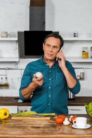 Photo pour Bel homme âgé moyen parler de smartphone et maintenant champignon en cuisine - image libre de droit