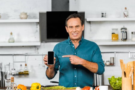smiling handsome middle aged man pointing on smartphone with blank screen in kitchen