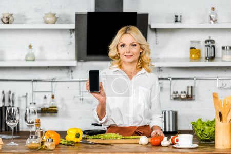 Photo pour Jolie femme âgée moyenne montrant smartphone avec écran blanc en cuisine - image libre de droit