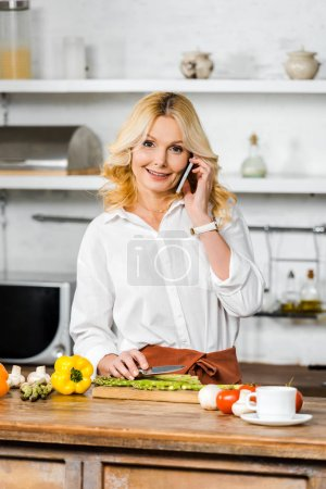 Photo for Attractive middle aged woman talking by smartphone while cooking in kitchen, looking at camera - Royalty Free Image
