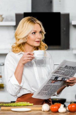 Photo pour Attrayant mature femme tenant tasse de thé et lecture journal d'affaires dans la cuisine - image libre de droit