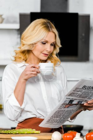 beautiful middle aged woman holding cup of tea and reading newspaper in kitchen