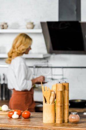 Photo pour Mise au point sélective de coupe portefeuille moyen femme âgée du thé dans la cuisine, les légumes et les ustensiles en bois sur table - image libre de droit