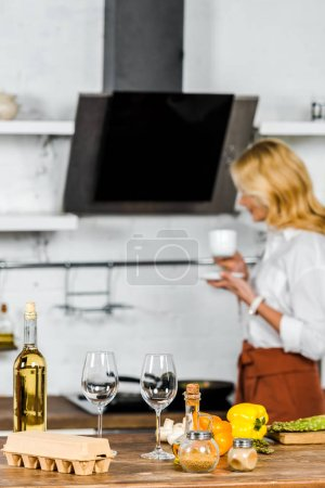 Photo for Selective focus of middle aged woman holding cup of tea in kitchen, vegetables and wine on tabletop - Royalty Free Image
