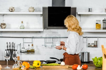 middle aged woman holding cup of tea in kitchen